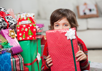 Boy Holding Christmas Gift In Front Of Face