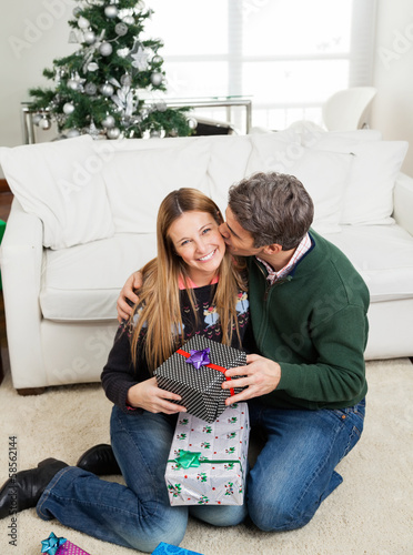 Man With Christmas Gift Kissing Woman On Cheek