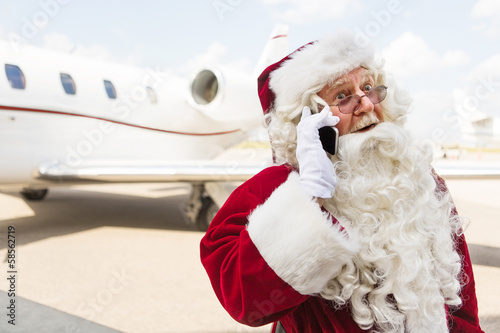 Foto op Plexiglas Luchthaven Surprised Santa Using Mobile Phone Against Private Jet