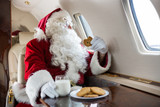 Santa Holding Cookie While Looking Through Private Jet's Window