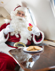 Santa Eating Cookies While Holding Milk Glass In Private Jet