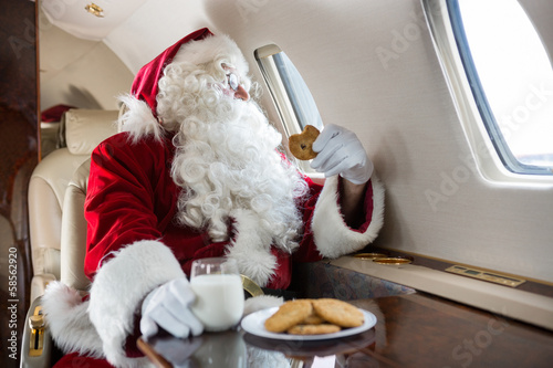 Airport Santa Holding Cookie While Looking Through Private Jet's Window