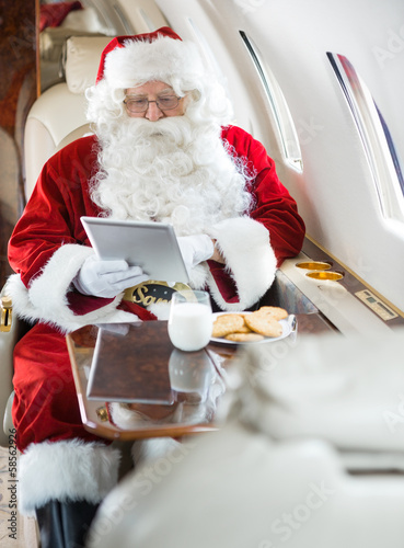 Santa Using Digital Tablet In Private Jet