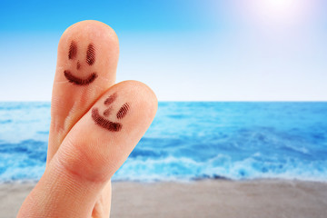 fingertips with smiley faces at the beach
