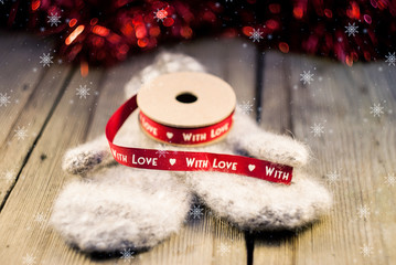 Knitted mittens with ribbon decoration With love on wooden backg