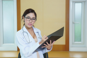 Young beautiful doctor writing on folder