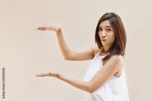 woman hand holding blank space on plain warm tone background