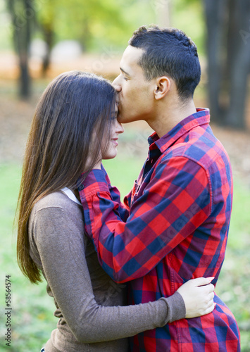 Close up of boy kissing girlfriend on forehead outdoor