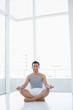 Full length portrait of a smiling man sitting in lotus pose