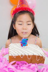 Cute little girl blowing her birthday cake