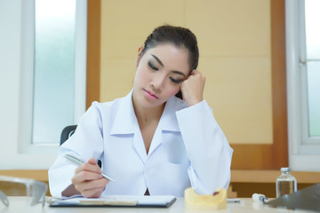 Bored woman dentist looking very boring at her desk