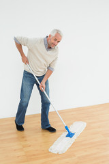 Full length portrait of a smiling mature man mopping the floor