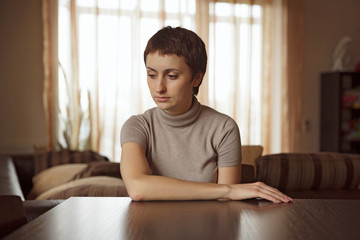 Beautiful sad woman sitting at the table
