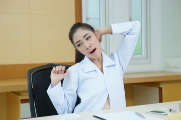 Tired female doctor stretching