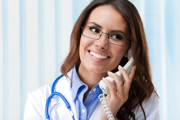 Young female doctor on phone, at office