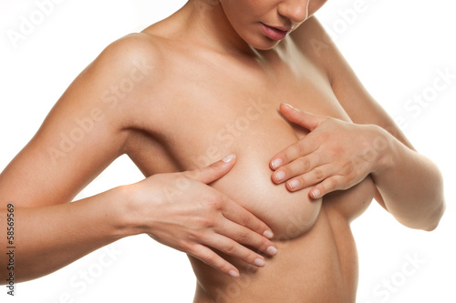 Woman manipulating her breast in a cancer check