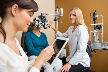 Eye Doctors Examining Senior Woman In Store