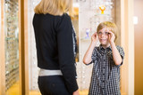 Boy Looking At Mother While Trying On Spectacles In Shop