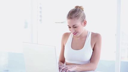 Sporty smiling blonde using laptop