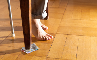legs of a man under the table, parquet floor
