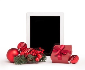tablet with red present box and christmas tree toys