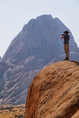A man filming the landscape in spitzkoppe, Namibia