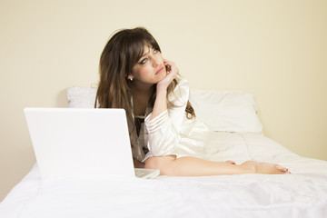 sad young woman in nightgown on compter on bed