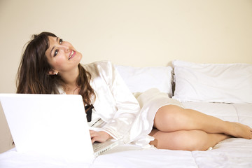 young woman in nightgown laying on bed with computer