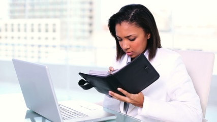 Concentrated young businesswoman writing into her diary