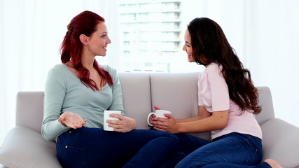 Two cute women sitting on couch while chatting
