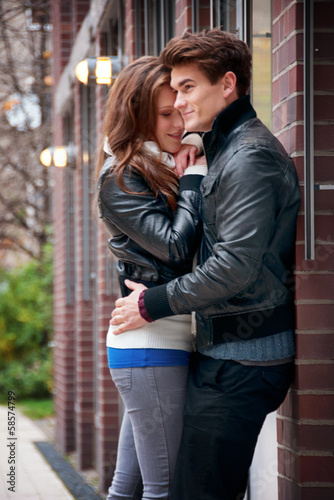 Young love couple hugging each other next to a house wall