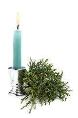 Blue candle with fir branch.