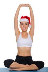 Asian girl doing yoga in a cap of Santa Claus
