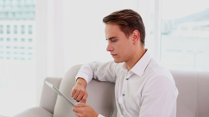 Serious young man using his tablet sitting on couch