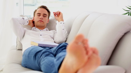 Attractive young man lying on couch while sleeping