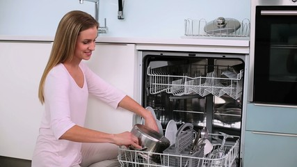 Beautiful calm woman filling the dish washer