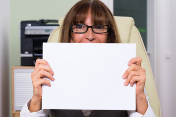 Businessfrau hält ein weißes Blatt Papier