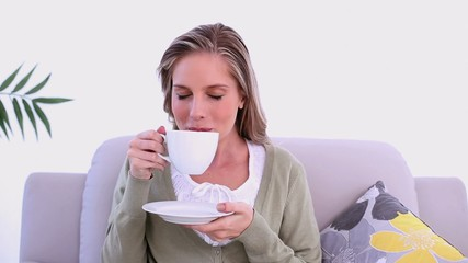 Content woman drinking from cup sitting on couch