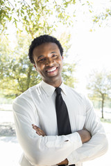 Smiling young business man with arms folded