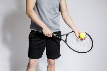 Athletic male holding tennis raquet and ball