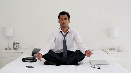 Happy handsome businessman meditating