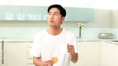 Attractive man eating cookie and drinking