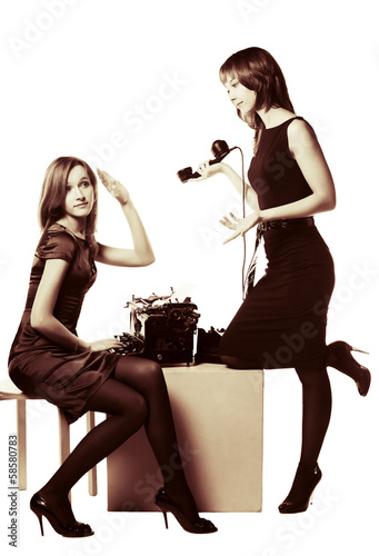 Two young women with retro phone and typewriter
