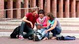 Happy students using tablet outside on steps