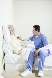 Male nurse listening to elderly woman's heartbeat