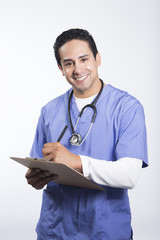 Smiling male nurse writing on clipboard