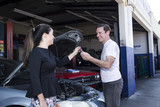 male mechanic fixing car for girl