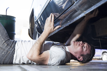 male mechanic working on a car