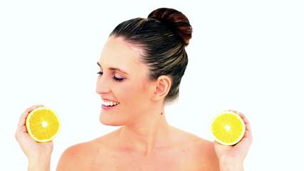 Pretty woman showing two orange halves