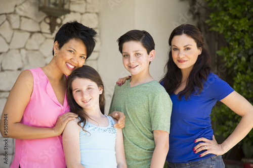 Family with same sex parents standing on porch